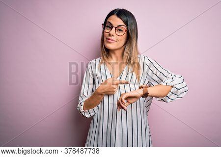 Young beautiful woman wearing casual striped t-shirt and glasses over pink background In hurry pointing to watch time, impatience, upset and angry for deadline delay