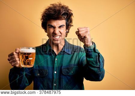 Young handsome man drinking jar of beer standing over isolated yellow background annoyed and frustrated shouting with anger, crazy and yelling with raised hand, anger concept