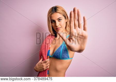 Beautiful blonde woman on vacation wearing bikini holding beach towel over pink background with open hand doing stop sign with serious and confident expression, defense gesture
