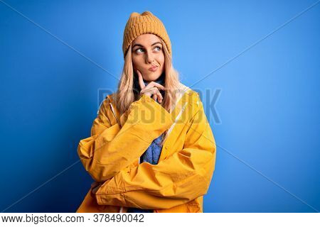 Young beautiful blonde woman wearing raincoat for rainy weather over blue background with hand on chin thinking about question, pensive expression. Smiling with thoughtful face. Doubt concept.