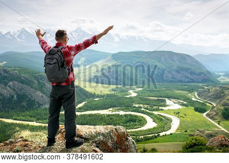 Man Arms Outstretched By The Mountains At Sunrise Enjoying Freedom And Life. Hiker.