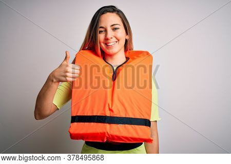 Young beautiful blonde woman with blue eyes wearing orange lifejacket over white background doing happy thumbs up gesture with hand. Approving expression looking at the camera showing success.