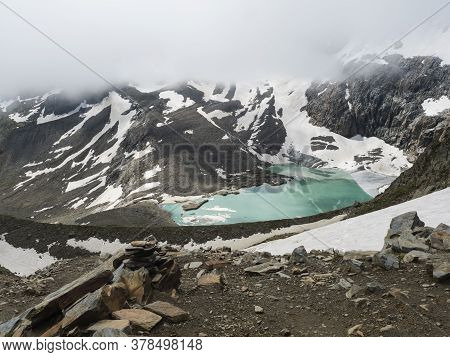Summer View Of The Sulzenauferner Glacier And Turquoise Glacial Lake And Waterfall From Melting Ice.