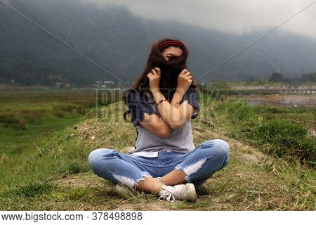 A Girl Sitting On The Ground, Hiding Her Face With Long Hair.