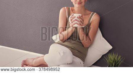 Beautiful Young Woman Sitting On Floor With Tablet