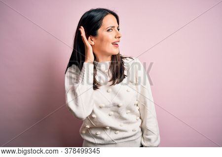 Young brunette woman with blue eyes wearing casual sweater over isolated pink background smiling with hand over ear listening an hearing to rumor or gossip. Deafness concept.