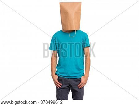 Portrait of teen boy with paper bag over head, isolated on white background. Child posing in studio.
