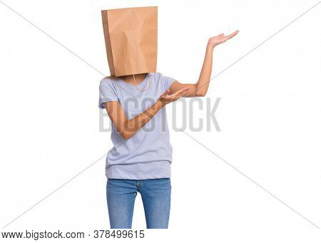 Teen girl with paper bag over head pointing finger away at copyspace, isolated on white. Teenager cover head with shopping bag pointing finger at something. Child pulling paper bag over head.