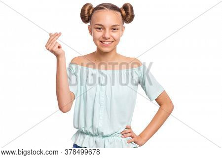 Portrait of young teen girl showing sign symbol of money by fingers, isolated on white background. Smiling child doing rich gesture. Teenager making cash sign gesture rubbing fingers together.