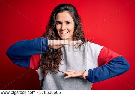Young beautiful woman with curly hair wearing casual sweatshirt over isolated red background gesturing with hands showing big and large size sign, measure symbol. Smiling looking at the camera.