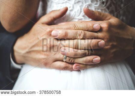 Close Up Of Groom's Palms Embracing Bride.