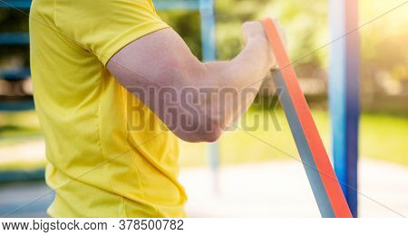 Male muscular arm with elastic rubber band in street