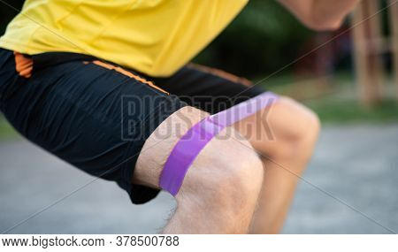 Man training knees using resistance band in street, close up