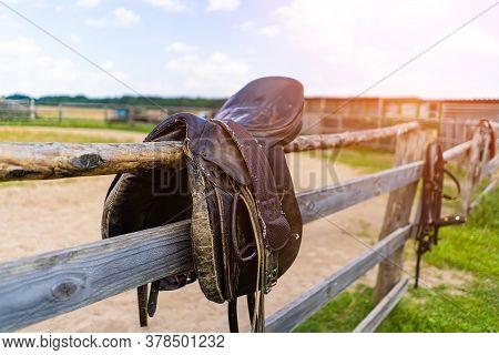 Horse Saddle Hanging On A Fence Close-up