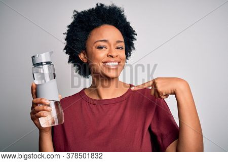 Young African American afro woman with curly hair drinking bottle of water for refreshment with surprise face pointing finger to himself
