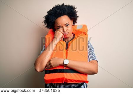 Young African American afro woman with curly hair wearing orange protection lifejacket thinking looking tired and bored with depression problems with crossed arms.