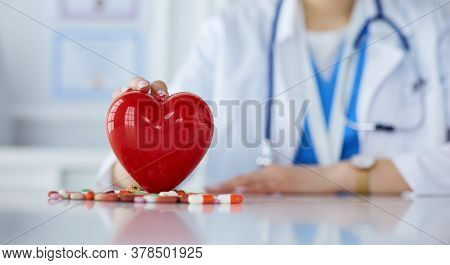 Doctor In White Coat With Stethoscope Holding Pills And Plastic Heart Isolated On White