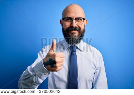 Handsome business bald man with beard wearing elegant tie and glasses over blue background doing happy thumbs up gesture with hand. Approving expression looking at the camera showing success.