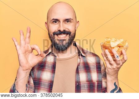 Young handsome man holding potato chip doing ok sign with fingers, smiling friendly gesturing excellent symbol