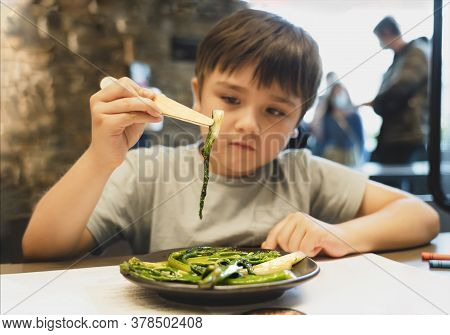 Kid Using Chop Stick Holding Pak Choi And Tenderstem Broccoli Fried With Oyster Sauce And Garlic, Ch