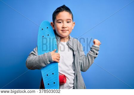 Young little boy kid skateboarder holding modern skateboard over blue isolated background pointing and showing with thumb up to the side with happy face smiling