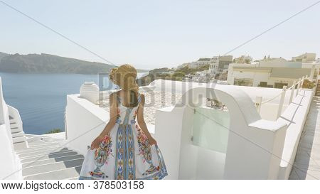 Back Side Of Woman Tourist Walking On Stairs In Oia Village, Santorini With The Mediterranean Sea. S