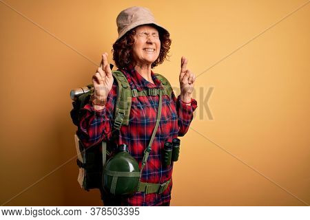 Middle age curly hair hiker woman hiking wearing backpack and water canteen using binoculars gesturing finger crossed smiling with hope and eyes closed. Luck and superstitious concept.