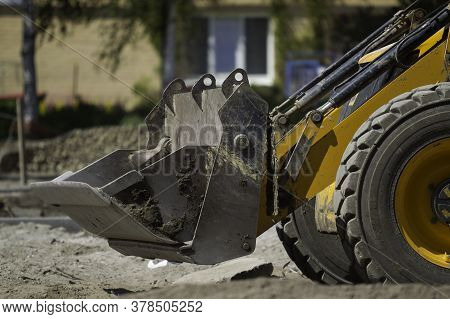 Front Loader, The Front Part With A Bucket And Wheels Close-up Performs Land Improvement Work On The