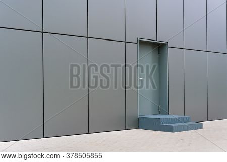 Local City Commercial Construction With Grey Blocks And Door At Stairs Near Paved Road Under Sunligh