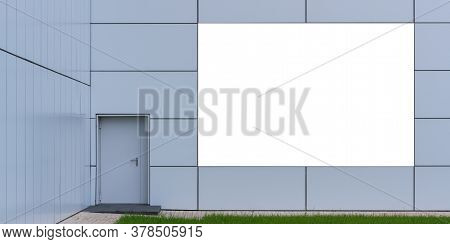 Blank Advertisement Banner Located On Commercial Building Wall Near Door Over Green Grass On Flowerb