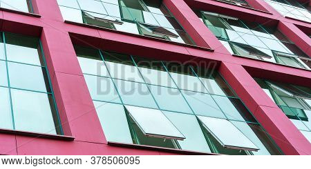 Corporate City Building Designed Wall With Red Beams Surrounding Panoramic Windows With Blue Skyscap