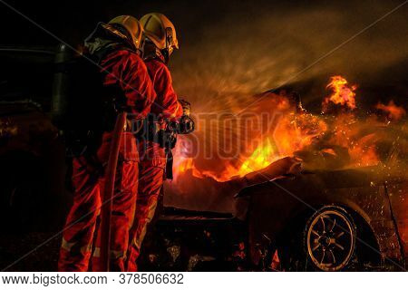 Firefighters use Twirl water fog fire extinguisher to fight with the fire flame from car accident of traffic collision in highway road. Firefighter safety disaster accident and public service concept.