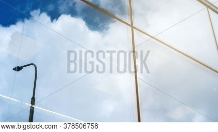 Large Commercial City Building Panoramic Windows Reflect Blue Sky With Fluffy White Clouds And Stree