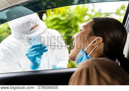 Portrait of asian woman drive thru coronavirus covid-19 test by medical staff with PPE suit by throat swab. New normal healthcare drive thru service and medical concept.