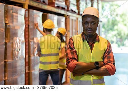 Portrait african black warehouse supervisor standing and crossed his arms in large warehouse distribution center with worker work on inventory in background. Business warehouse and logistic concept