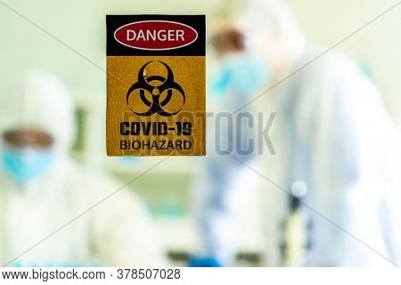 Caution danger Signage of COVID-19 coronavirus in front of Laboratory room with background of Scientists working and researching vaccine for ncov-19 virus for world pandemic situation.