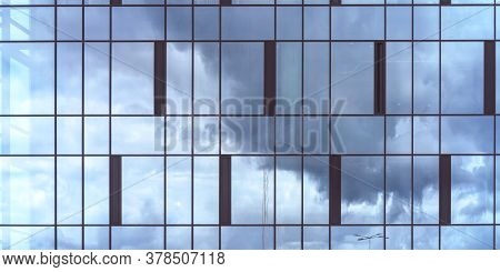 New Skyscraper With Commercial Office Windows Of Blue Colour Reflects Grey And White Clouds In Skysc