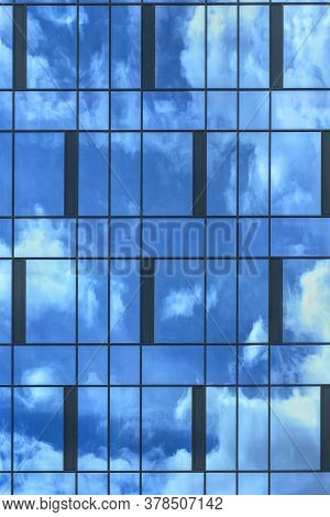 Blue Sky And White Clouds Reflect In Highrise Office Building Panoramic Windows On Summer Day Close