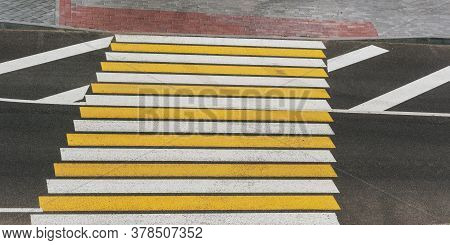 New Pedestrian Crosswalk With White And Yellow Lines On Grey Asphalt Road In City Centre On Summer D
