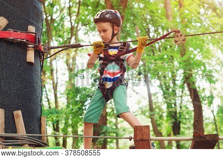 Little Boy In The Rope Park Pass Obstacles. Cute Kid Climb The Rope Road. Adventure Climbing High Wi