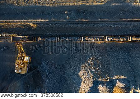 Excavator Loads Ore Into Freight Cars Aerial Top View