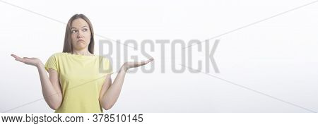 Isolated Young Caucasian Woman Shrugs Her Shoulders And Spread Hands With Questioned Face Emotion An