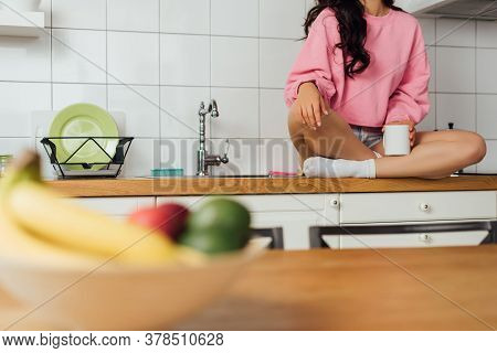 Cropped View Of Young Woman Holding Cup Of Coffee On Worktop In Kitchen
