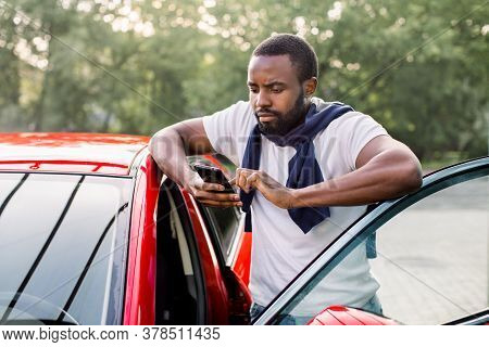 Concentrated Young African Man Using His Smart Phone To Check The Status Or Control His Car Insuranc