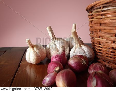 Shallots And Garlic Beside The Wicker Basket On A Wooden Table