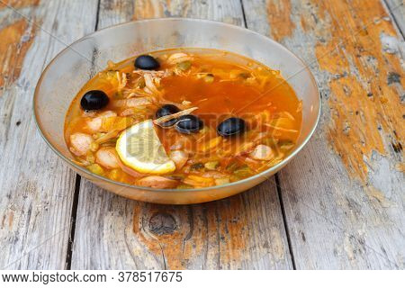 Freshly Cooked Solyanka Soup (solyanka) With Lemon, Meat, Pickles And Olives On An Old Board Table