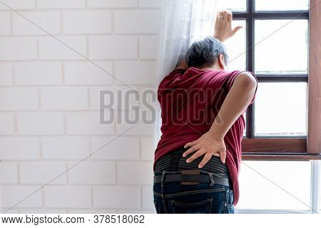 Middle-aged Asian Man Standing By The Window, Having Pain In His Back Muscles, In The Middle Of The