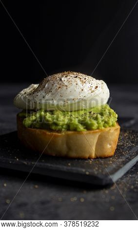 Poached Egg On Avocado Cream And Bread Toast On Dark Background With Copyspace