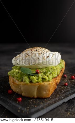 Poached Egg On Avocado Cream With Peppercorns And Bread Toast On Dark Background With Copyspace