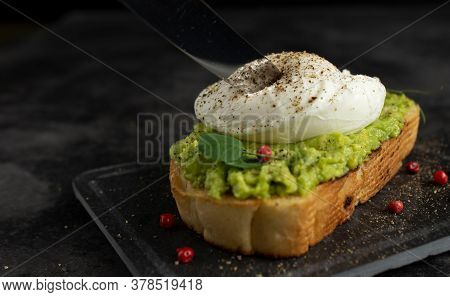 Knife Blade Cuts Poached Egg On Avocado Toast With Peppercorns And Microgreen